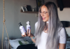 Meisje met lang zilvergrijs haar houdt de zilvershampoo en zilvermasker in haar hand
