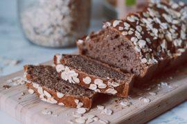 Plakjes gezonde ontbijtkoek op houten snijpank met marmeren achtergrond