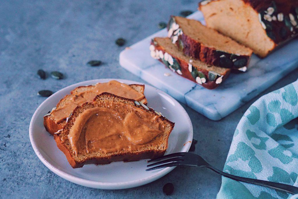Pumpkin protein cake in plakjes gesneden met pindakaas op marmeren tafel