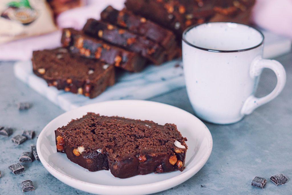Fudgy gezonde chocolade cake plak op bordje met kopje koffie ernaast