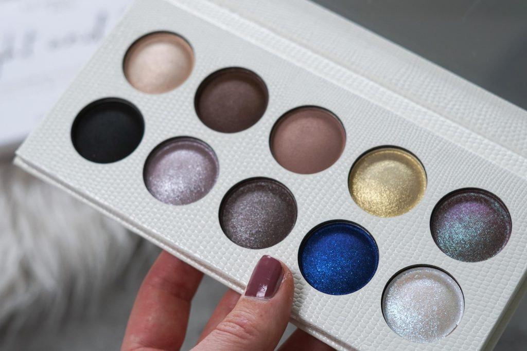 Revolution PRO eyeshadow palette Night & Day met glinsterende oogschaduw kleuren vastgehouden in hand