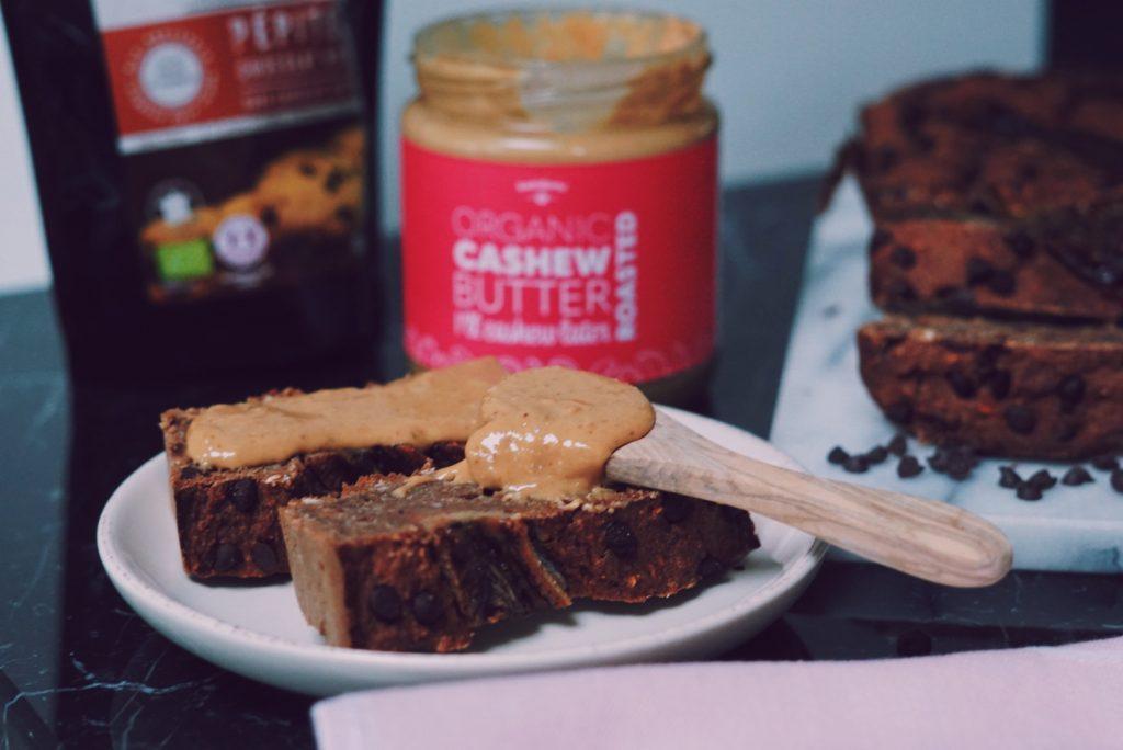 Kaneel bananenbrood met chocolade stukjes op bordje met een lepel notenpasta