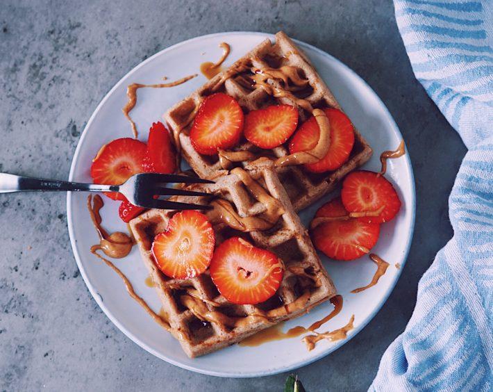 Glutenvrije wafels met aardbeien en pindakaas op lichtgrijs bordje