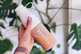 Kencko smoothie in wit flesje met planten op achtergrond