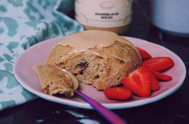 Healthy mugcake met teffmeel op een roze bordje met aardbeien ernaast